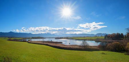 rural landscape with moor lake riegsee and bavarian alps, bright sunshine and blue sky with copy space. 免版税图像