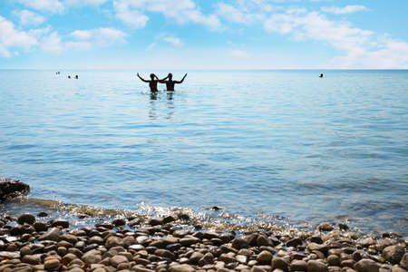 two girls silhouettes in the blue water, gravel beach and beautiful sky with clouds