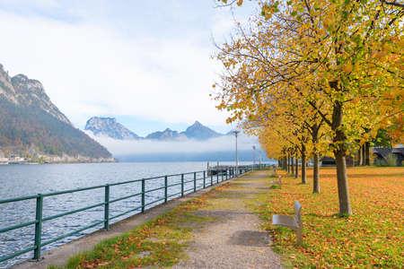lakeside promenade Unterlangbath, traunsee lake with mountain view and autumnal trees, austrian tourist resort 免版税图像