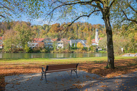 Isar riverside with autumnal trees and bench, spa town Wolfratshausen, beautiful destination upper bavaria Stock fotó