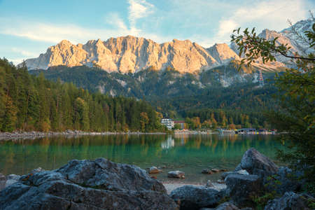 lake shore Eibsee with rocks and view to bavarian mountains, zugspitze mass tourist resort