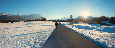 man takes an evening walk in wintry landscape Buckelwiesen, with view to Karwendel mountains