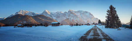 country road in beautiful winter landscape Buckelwiesen, evening in the bavarian alps, with view to karwendel mountains