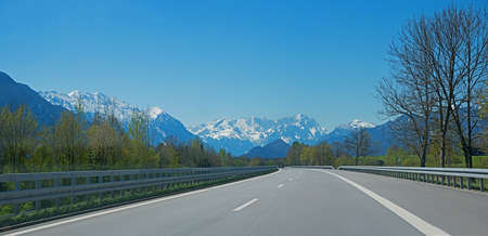 highway to Garmisch, with some cars, view to Wetterstein mountains, at springtime. upper bavaria landscape, blue sky with copy space.