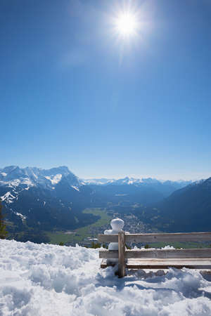 little snowman sitting on a wooden bench, looking intothe landscape of bavarian alps. bright sunshine and blue sky