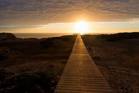 wooden boardwalk at sunset, coastal landscape Carrapateira West Algarve. cloudy sky and sunshine
