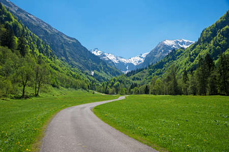 stunning spring landscape, walkway through Trettach valley, view to snowy allgau alps, south germany. blue sky with copy space Standard-Bild