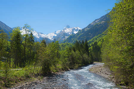 stunning spring landscape, Trettach river and valley, view to snowy allgau alps, south germany