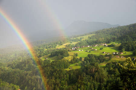 foggy mountain landscape with double rainbow and view to Conters village, prattigau switzerland, canton grisons