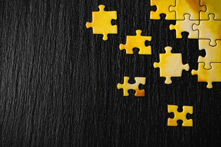 Yellow puzzle on a black stone background. Frame from puzzle around negative space.