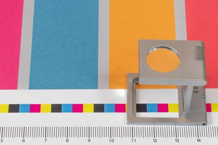 Silver magnifying glass standing on the test print, colored background. Print loupe on offset printed sheet with basic colors control bars.