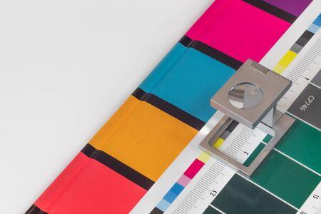 Lente d'ingrandimento d'argento in piedi sulla stampa di prova, sfondo colorato. Lente di stampa su foglio stampato in offset con barre di controllo dei colori di base.