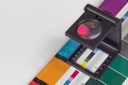 Lupa negra de pie sobre la impresión de prueba con fondo de color. Lupa de impresión en hoja impresa en offset con barras de control de colores básicos.