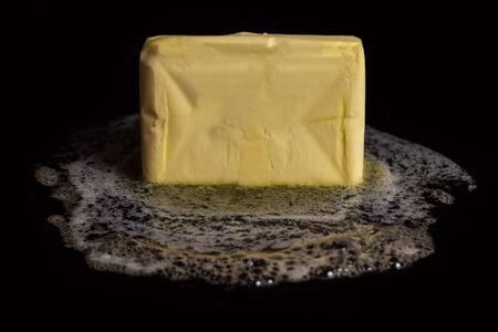 A cube of butter melting on a black plate on black isolated background. Stock Photo