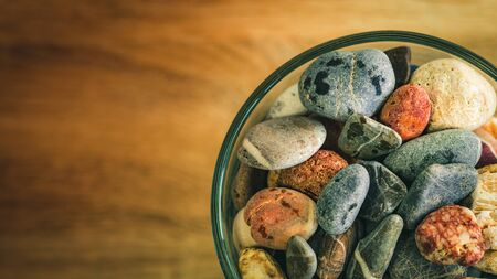 Small sea stones in a glass vessel. The idea of decorating the house with small rocks in a jar on a wooden blurred background.