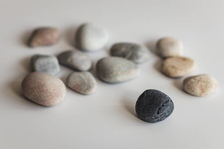 The concept of exclusion from the group made using colored stones on a white background. A reference to racism and religious, sexual or ideological intolerance. 写真素材