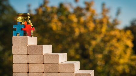 Teamwork concept. The concept of victory. Two puzzles stand at the top of the stairs made of wooden blocks on a blurred autumn background on a sunny day.