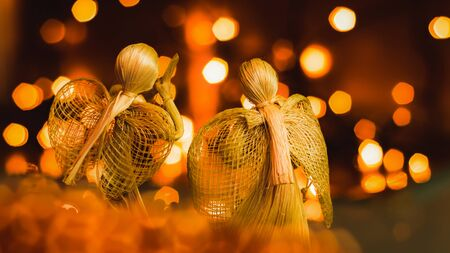 Two straw angels praying on a blurred Christmas background. Beautiful bokeh created by Christmas lights. Traditional hand-made doll as a Christmas tree decoration.
