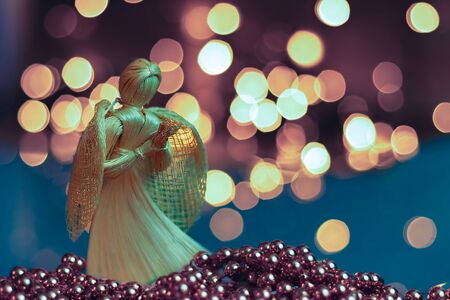 Straw angel praying on a blurred Christmas background. Beautiful bokeh created by Christmas lights. Traditional hand-made doll as a Christmas tree decoration. 免版税图像