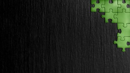 Green puzzle in the corner of the image on a black natural stone background of slate. A frame with an empty space for your description.