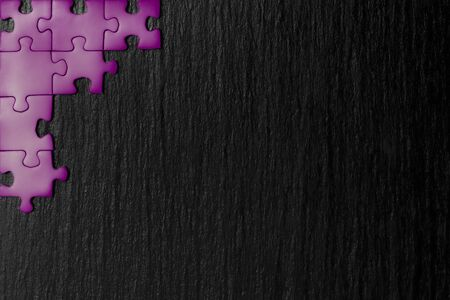 Purple puzzle in the corner of the image on a black natural stone background of slate. A frame with an empty space for your description. 免版税图像