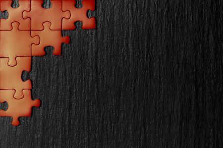 Red puzzle in the corner of the image on a black natural stone background of slate. A frame with an empty space for your description. 免版税图像