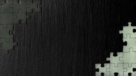 Black nd white puzzle in the corner of the image on a black natural stone background of slate. A frame with an empty space for your description. 免版税图像