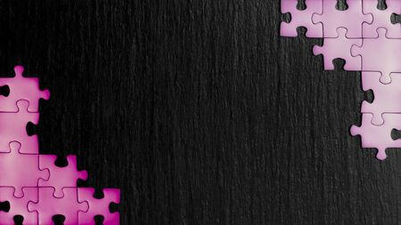 Pink puzzles in the corners of the image on a black natural stone background of slate. A frame with an empty space for your description. 免版税图像