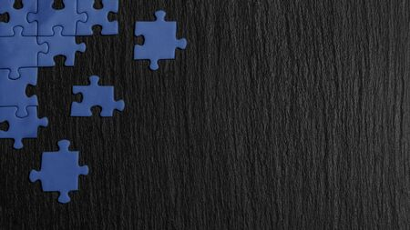 Blue puzzle in the corner of the image on a black natural stone background of slate. A frame with an empty space for your description.