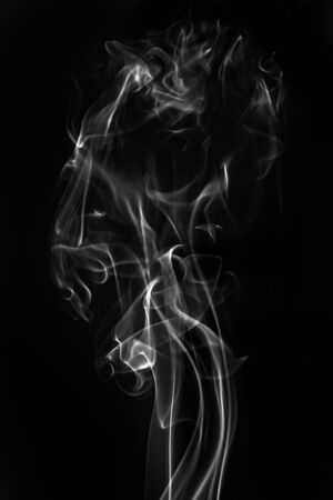 Gray smoke on a black background. Realistic incense smoke captured with a flash. 免版税图像