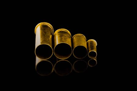 Comparison of sizes of different used bullet shells on a black isolated background with reflection from a tin table top. View of the different caliber cartridges. 免版税图像
