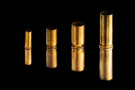 Comparison of sizes of different used bullet shells on a black isolated background with reflection from a tin table top. View of the different caliber cartridges. Stock Photo