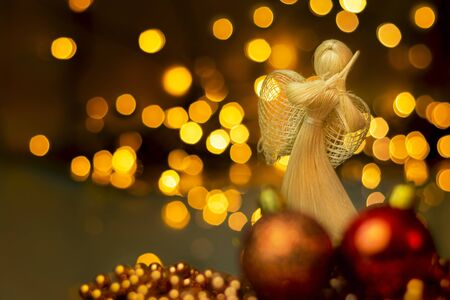 Traditional hand made straw doll with Christmas ornaments on a blurred background with lights. Dramatic Christmas landscape with dried straw angel who prays. A christmas tree decoration.
