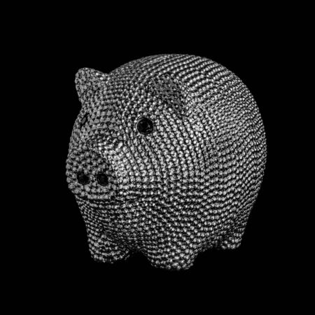 Silver metal piggy bank with black eyes isolated on black background.