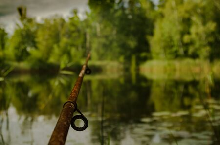 Old rusty fishing rod on a blurry background with a lake and trees. 免版税图像