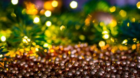 Christmas landscape with shiny balls from a Christmas chain with a blurred background of Christmas lights and Christmas tree branches. 免版税图像