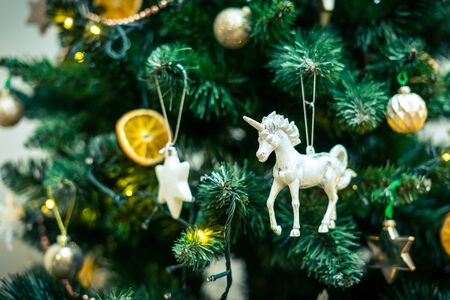 White unicorn as a Christmas tree ornament hanging on a Christmas tree in the company of baubles, an orange patch and white stars. 免版税图像