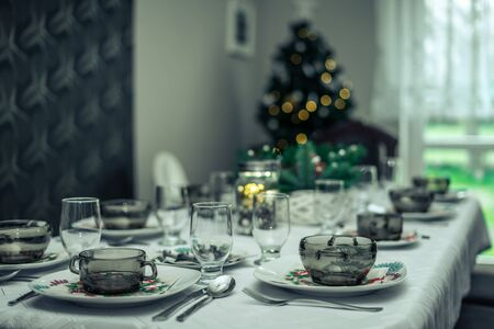 A set christmas table with a christmas tree on blurry background.