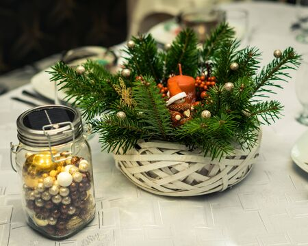 Christmas basket of pine twigs, Christmas decorations, a little gnome, red candle and rowan fruit standing next to a decoration made of a jar with baubles inside