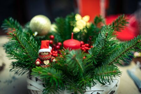 Christmas basket made of pine branches, Christmas decorations, little elves, red candles and rowan fruit. 免版税图像