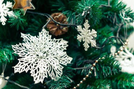 Christmas decorations, white flower with yarn, Christmas ornament and white star. Beautiful view of the Christmas tree with blurry background.