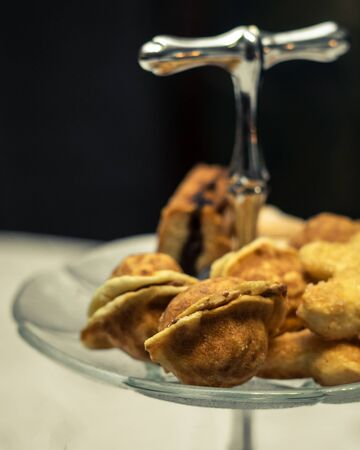 Walnut shaped biscuits stacked on a glass tray with a silver handle. Selective focus