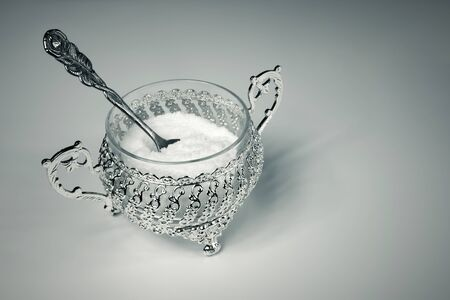 Xylitol in a metal decorative bowl with a rose-shaped spoon. Xylitol, a substitute for birch sugar for diabetics. A beautiful silver sugar bowl with xylitol or white sugar.