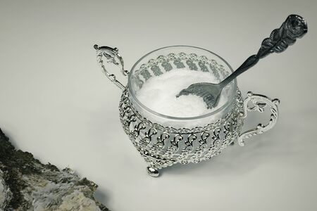 Xylitol in a metal decorative bowl with a rose-shaped spoon. Xylitol, a substitute for birch sugar for diabetics. A beautiful silver sugar bowl with xylitol or white sugar. Birch bark in the corner.