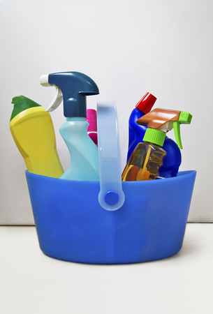Bottles of cleaners in blue plastic basket photo