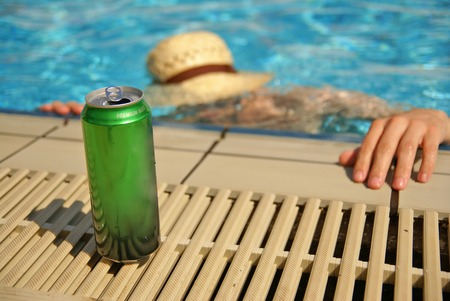 Can of beer by the swimming pool and drowning drunk man in the background