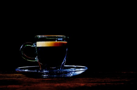 glass cup: Glass coffee cup on the table, black background Stock Photo