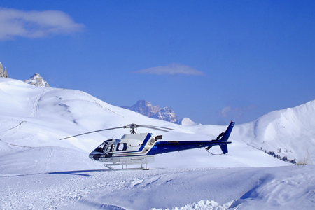 skiing accident: Rescue helicopter in the mountains and blue  sky in the background