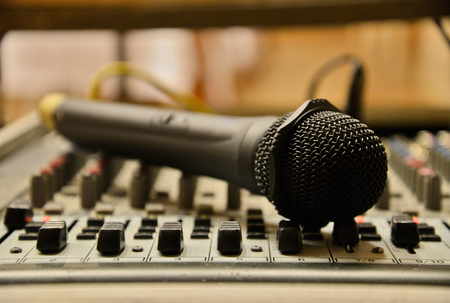 Close up of black mic on the mix pult. Music theme. Professional audio equipment.