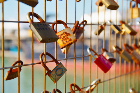 Close up of several locks with names on the fence. Love forever concept.